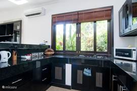 Spacious kitchen with 3-burner gas-burner hob, fridge / freezer, microwave oven, coffee machine, kettle, blender, pots, pans, dishes, glasses, cutlery.