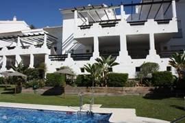 De tuin met zwembad met zicht op het appartement