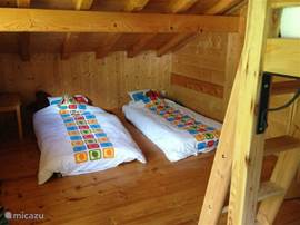 Chalet Haute bergen, Chamonix Mont Blanc. In deze slaapkamer staat ook een stapelbed. De kamer heeft een deur die toegang geeft tot het balkon.