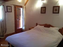 Chalet Haute bergen, Chamonix Mont Blanc. De masterbedroom, ingericht in de typische Savoyaardse stijl. Ruime slaapkamer met kledingkasten en deur naar balkon.