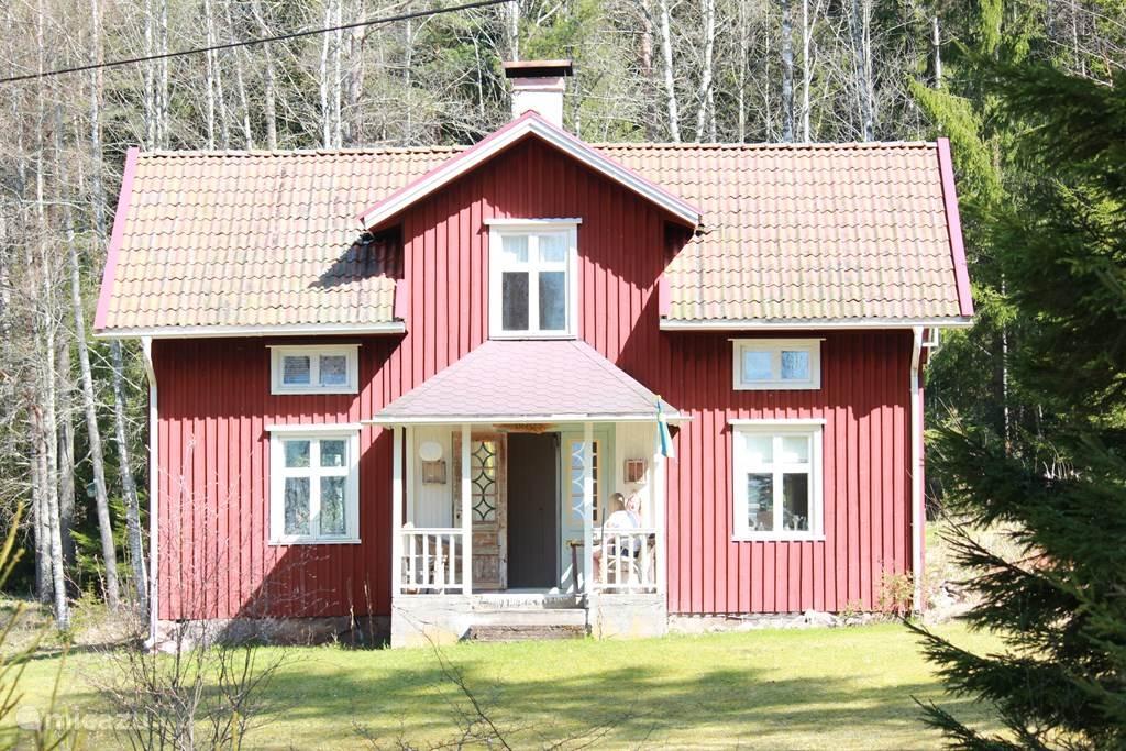 Krakviken, het vakantie huis gezien vanaf de voorzijde, met veranda en ruime tuin.