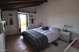 Master bedroom met privé-badkamer en met openslaande deuren en balkon met adembenemend uitzicht.