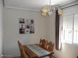 Een mooie woonkamer met licht eiken eettafel en 4 stoelen. Alle ramen van het huis zijn voorzien van rolluiken en er hangt een airco unit in de woonkamer om de temperatuur binnen heerlijk koel te houden in de zomer.