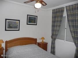 Ruime 2p slaapkamer op de begane grond met een tweepersoonsbed, inbouwkast met veel ruimte, 2 nachtkastjes met bedlampjes, rolluiken om de slaapkamer volledig te verduisteren (handbediening).