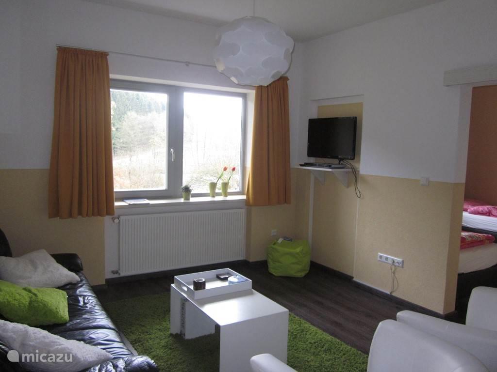 De woonkamer, met aangrenzend de slaapkamer. Tijdschriften, boeken, dvd's en spelletjes zijn aanwezig