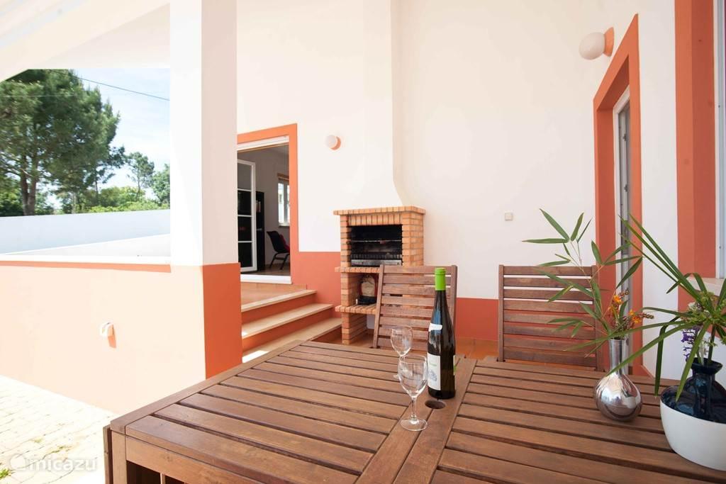 De veranda met tuinmeubilair en barbecue