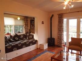 woonkamer met erkerbank en houtkachel
