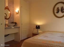 slaapkamer met kledingkasten en wastafelcombinatie