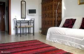 De woon/slaapkamer vanaf balkonkant, 2x eenpersoons bedbanken, linnenkast, eettafel, TV-DVD, halletje met badkamer en kitchenette