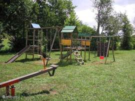 Playset with 2 slides, swings and climbing tower and climbing wall.