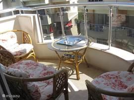 balkon van woonkamer met tuinstoelen uitzicht naar zwembad