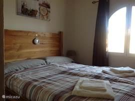 In deze slaapkamer staat een romantisch bed. Dit bed is ook voorzien van extra lange matrassen 80x210
