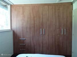 in grote slaapkamer een garderobe kast met spiegel inside en veel opbergruimte