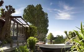 Tuin grenzend aan water met boot voor 6 personen en motor