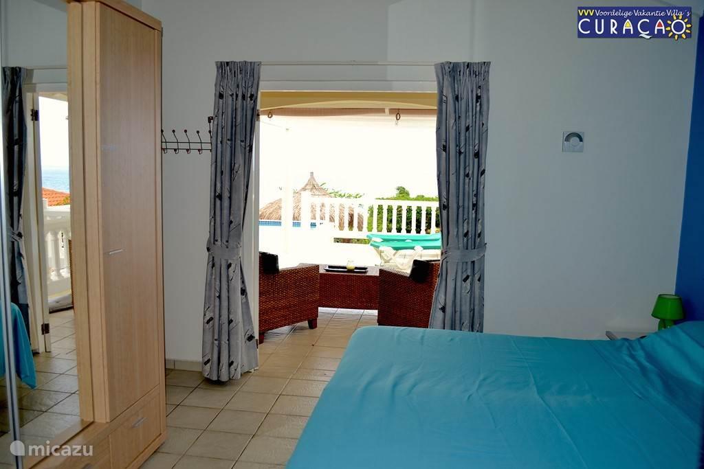 Slaapkamer:   Masterbedroom, openslaande deuren naar de porch, met uitzicht over terras, zwembad en oceaan.