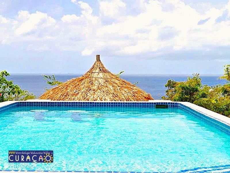 In het zwembad vindt u zitjes om heerlijk over de rand van het zwembad, te genieten van het 180 gr. uitzicht over de oceaan.  Hier ziet u nog een puntje van de lager gelegen palapa, waar u heerlijk in de schaduw van de tuin en het uitzicht kunt genieten.