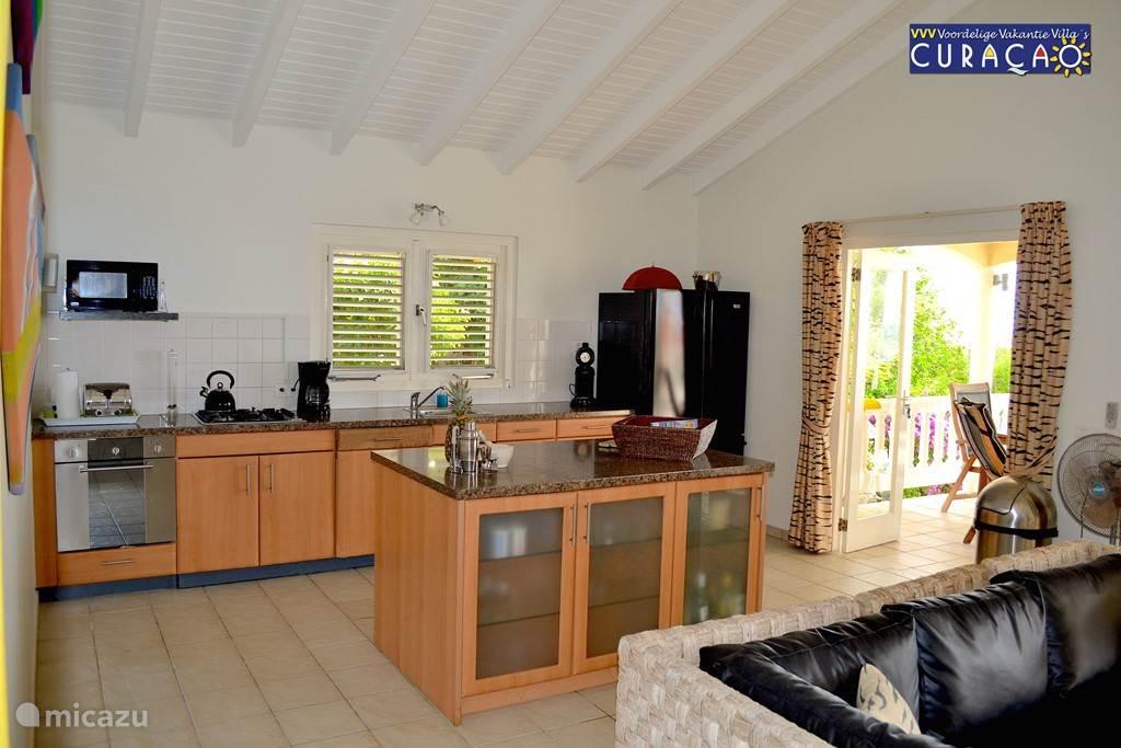 Ook bij de keuken brede schuifdeuren die toegang geven tot het grote terras, pooldeck en zwembad.