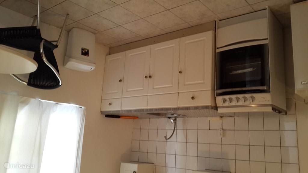 Keuken met oven en koelkast, pannen, servies, bestek en keukenapparaten.