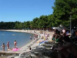 Een heerlijk baai waar men heerlijk kan zwemmen op het strand kan zonnen of heerlijk onder de bomen genieten van het uitzicht