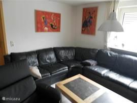 mooie zitkamer met groot lederen hoekbankstel, lederen fauteuil , grootbeeld flatscreen, film en muziek bibliotheek op harde schijf xbox 360
