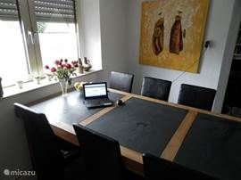 The dining room has a large 8 seater dining table.