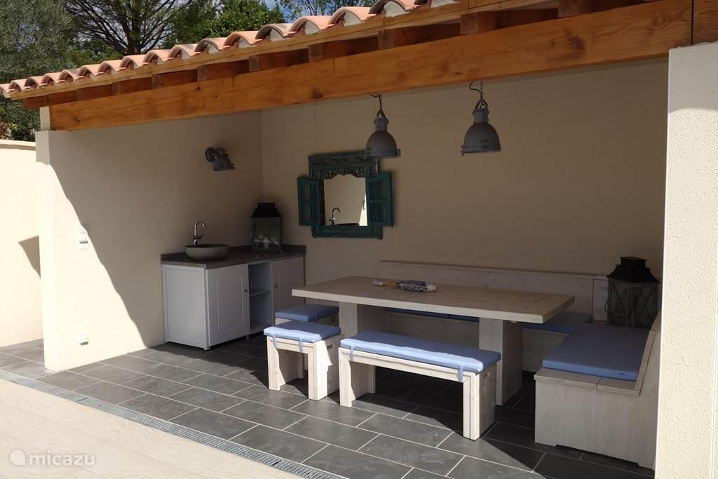 Het zwembadhuis. Rechts van deze open ruimte is een deur naar de technische installaties en een toilet.
