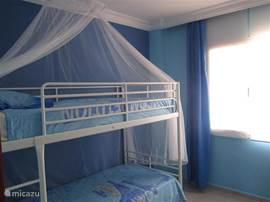 Ocean Bedroom, relaxerende dubbele kamer met stapelbed en ventilator (bewuste keuze voor de kinderen). Ook al zijn alle ramen van de villa voorzien van vliegenramen biedt dit extra muggennet uw kinderen rustige nachten... Bedlinnen incl.