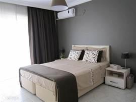 Master Bedroom. Zeer ruime stijlvolle 2pers.kamer met King Size bed, airco, balkon en zeezicht! Bedlinnen incl.