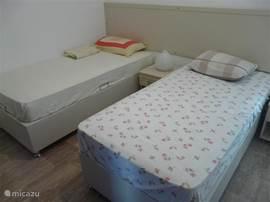 slaapkamer op de tweede etage met twee eenpersoonsbedden en tuindeuren naar een dakterras.