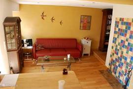 The living room consists of two parts. There is a sitting area with armchairs, coffee table and sofa. In the reading room slightly lower, a second sofa and coffee table, also a wood burning stove and well stocked bookcase. There is a small TV, DVD player and a CD player There are games, DVDs and CDs.