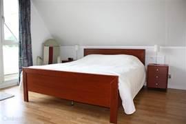Slaapkamer met 2-persoons ledikant m{met kinderledikant en kleuterbed)met openslaande deur naar overdekt balkon