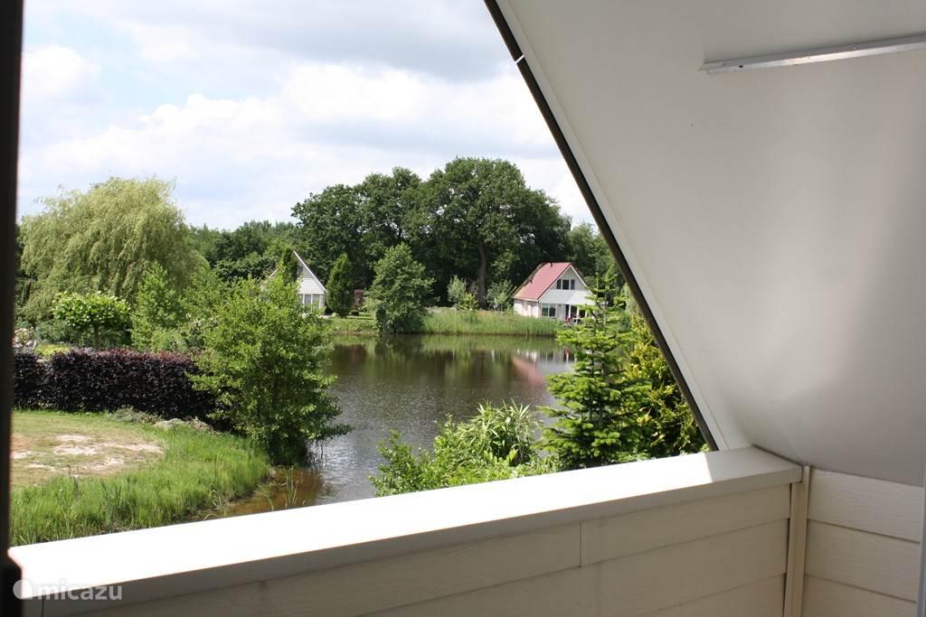 Vanuit overdekte balkon zicht op de zwemplas