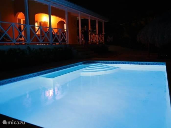 Zwembad bij avondlicht.  Een kant van het zwembad is voorzien van een zitgedeelte.