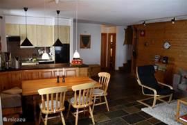 De eettafel en daar achter de open keuken. Achter in de kamer zie je de toegang tot 1 van de slaapkamers (rechts)