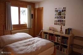 De 2-persoonsslaapkamer met achterin de deur naar de kleine, aangrenzende badkamer.