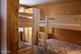 De 2e slaapkamer bij binnenkomst gefotografeerd. Te zien is een grote kledingkast rechts achterin . Onder de bedden bevinden zich nog 2 opberglades.