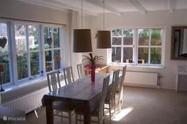Lichte ruime woonkamer met grote eethoek.