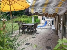Achterterras met tuinmeubelen en parasol.