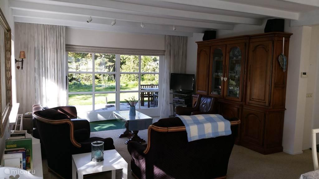 Ruime gezellige woonkamer met openslaande deuren naar eigen tuin met  groot terras op ZW.