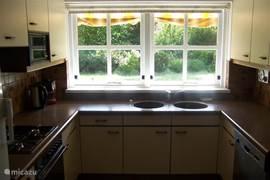 Aparte keuken met allerhande noodzakelijke benodigdheden met zicht op tuin.