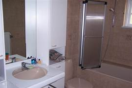 Badkamer op begane grond met ligbad en douche, wastafel en WC.