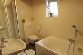 Badkamer met ligbad, losse douche en toilet.
