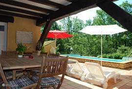 Vanaf het overdekte terras kijkt u hier naar het zwembad en de tuin. Altijd goed toeven hier, ofwel om de schaduw op te zoeken ofwel om de droogte op te zoeken.