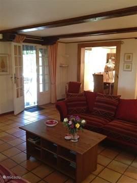 Hier kijkt u niet alleen naar de eetkamer vanuit de woonkamer maar ook naar de openslaande deuren naar het overdekte terras.