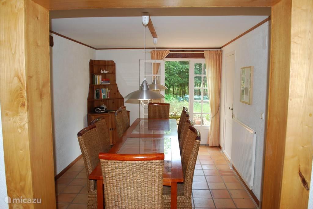 De eetkamer voor 10 personen met openslaande deuren naar het terras (de eetkamer grenst aan de open keuken en woonkamer).