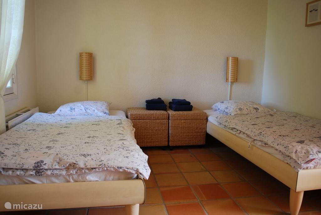 Deze kamer is beneden en grenst aan het terras met openslaande deuren. Tevens heeft deze kamer een eigen wastafel op de kamer.