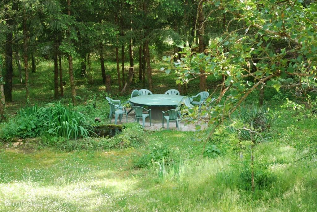 Er is een enorme achtertuin en een flink stuk bos wat bij het huis hoort. Hier een foto van een zitplek in de tuin, een grote ronde tafel bij de vijver. Lekker wat verkoeling onder de bomen.