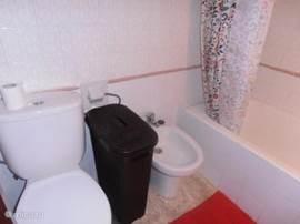 badkamer met toilet ,bidet en ligbad ,douche achter gordijn