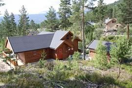 Achteraanzicht bungalow vanaf heuvel die bij de tuin hoort.