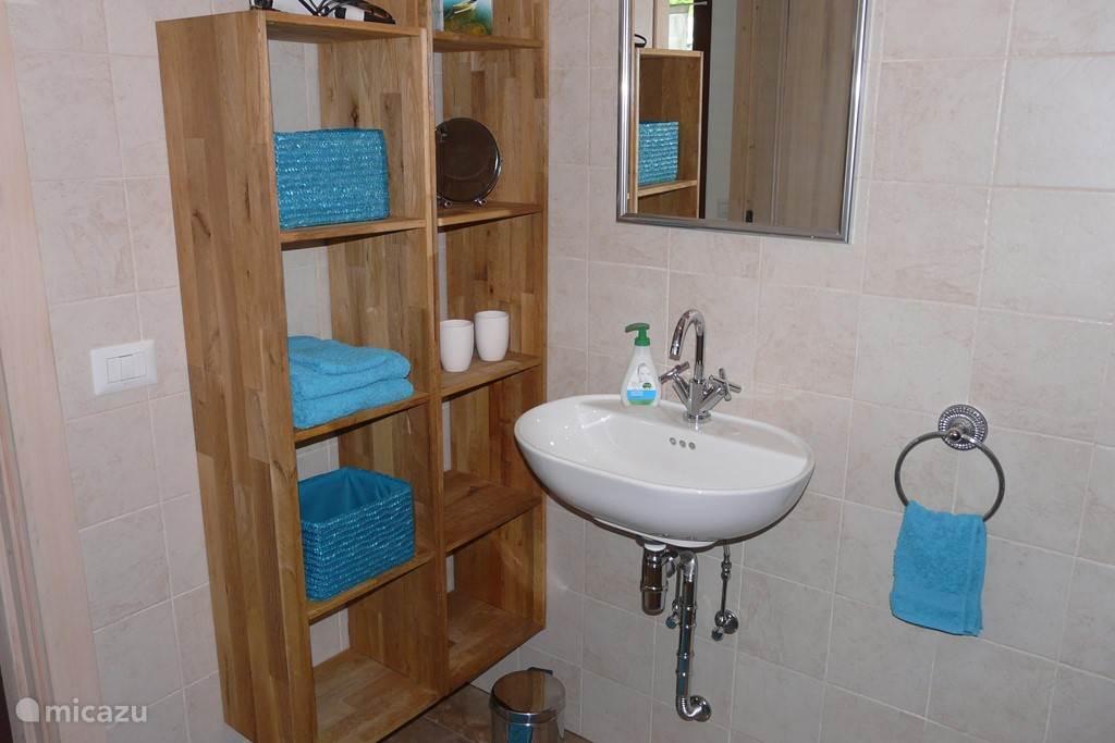 Een badkamer met afdoende bergruimte.